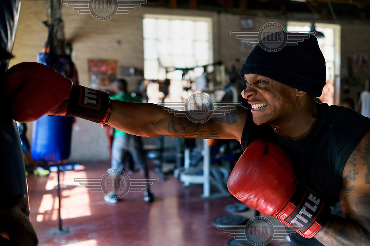 'Taf Jam' working a punch bag at the Hillbrow Boxing Club. After gunshot injuries put an end to his own boxing career, George Khosi founded the club to instil discipline, camaraderie and an activity away from the streets for young people from the community, and also to provide a training space for upcoming professional boxers. The club operates in a donated space on the forecourt of a disused petrol station in Hillbrow, one of the country's most notorious neighbourhoods.