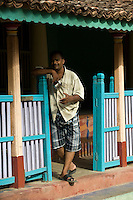 Man looking out from railing in front of his home. Thittacheri.<br /> Tamil Nadu. South India.