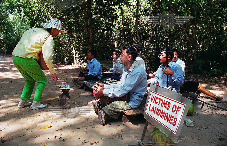 Amputee mine victims play music for tourists near the ruins of the Angkor temples..
