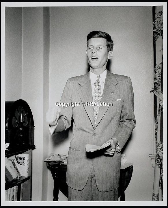 BNPS.co.uk (01202 558833)<br /> Pic: RRAuction/BNPS<br /> <br /> JFK is seen in his Beacon Hill apartment practicing a speech, with his favorite book, Pilgrim's Way, by his side on the shelf below the radio.<br /> <br /> Incredibly-rare photos highlighting the first foray into politics for John F. Kennedy that would eventually cost him his life have come to light.<br /> <br /> The 100 black and white snaps show a youthful-looking JFK from 1946, when he was campaigning to become a US congressman for the first time.<br /> <br /> The tragic future president is seen during an oration lesson where he was given help by an expert with public speaking and posture.<br /> <br /> The 29-year-old is also depicted mingling with the public at an annual parade and as well as celebrating his first political victory - a congressional primary vote - in June 1946.<br /> <br /> The images are being sold by US-based RR Auction.