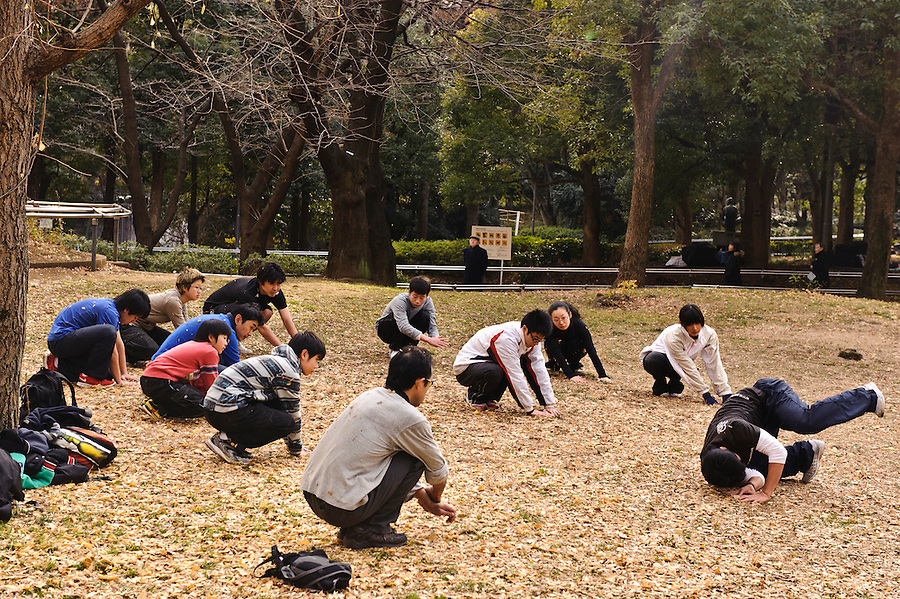 """Parkour instructor Jun """"Sullivan"""" Sato demonstrates a roll. Parkour Tokyo group practice, Shinjuku Chuo Koen, Tokyo, Japan, January 15, 2012. Parkour is a modern method of physical training, also known as freerunning. It was founded in France in the 1990s. There is a small group of around 50 parkour practitioners in Tokyo."""