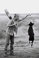 Young man holding guitar and ball, playing with dog (B&amp;W)
