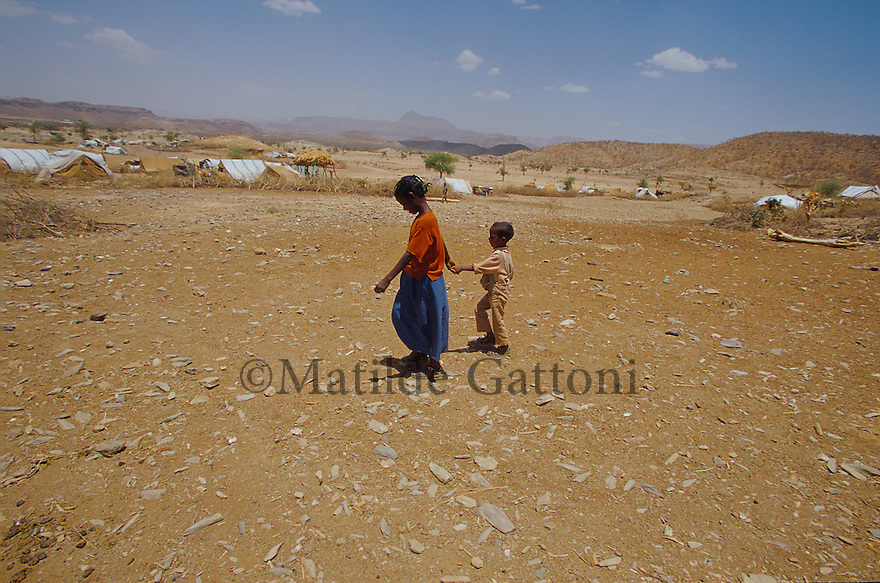 Eritrea - Debub- Little girl walking with her brother in an IDP camp. As a result of 30 years of war for independence against Ethiopia (from 1961 to 1991) and another 3 years from 1997 to 2000, there are 50,000 Eritreans currently living in internally displaced (IDP) camps throughout the country. These IDPs have fled three times in the last 10 years, each time because of renewed military conflict. They lived in relatives' homes when lucky enough, but mostly, the fled to the mountains, where they attempted to do what Eritreans do best, survive. Currently there is no Ethiopian occupation in Eritrea, but landmines prevent the IDPs from finally going home. .It is estimated that every Eritrean family lost two or three members to the war which makes the reality of the current emergency situation even more painful for Eritreans worldwide. Currently, the male population has been decreased dramatically, affecting the most fundamental socio-economic systems in the country. Among the refugee population, an overwhelming majority of families are female-headed, severely affecting agricultural production. For, IDPs in particular, 80% of households are female-headed..The unresolved border dispute with Ethiopia remains the most important drawback to Eritrea's socio-economic development, as national resources (human and material) continue to be prioritized for national defense. Eritrea is vulnerable to recurrent droughts and variable weather conditions with potentially negative effects on the 80 percent of the population that depend on agriculture and pastoralism as main sources of livelihood. The situation has been exacerbated by the unresolved border dispute, resulting in economic stagnation, lack of food security and increased susceptibility of the population to various ailments including communicable diseases and malnutrition. .