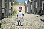 """A child stands on a path amid houses in a model resettlement village constructed by the Lutheran World Federation in Gressier, Haiti. The settlement houses 150 families who were left homeless by the 2010 earthquake, and represents an intentional effort to """"build back better,"""" creating a sustainable and democratic community. This boy and his mother are among the residents."""