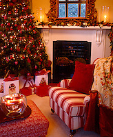 A Christmas tree with presents arranged at the base in a red themed living room