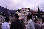 a crowd gathers to examine the damaged remains of what was the Pakistani Army headquarters for their anti-militant campaign in Swat before the building was destroyed by a suicide bomber who rammed a bomb laden vehicle into its gate.  the militants have been carrying out a sustained campaign against army and civilian targets despite the presence of nearly 30,000 Pakistani Army soldiers in the area