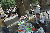Selling Islamic religious leaflets and book outside of the Juma Mosque, after friday prayers,  in the Old Silk Road city of Kokand in the Ferghana valley. The Ferghana valley is now a growing hotspot of Islamic Fundamentalism in the Central Asian republics. Uzbekistan.