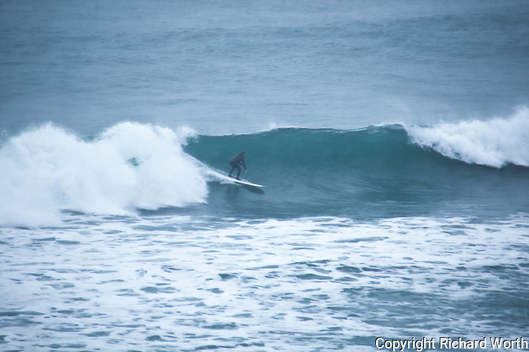 Precusors of the storms to come, waves come ashore at Montara State Beach south of San Francisco and a surfer rides this early storm wave.