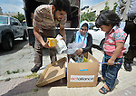 Ruba Abu Humaid (center), a refugee from Damascus, Syria, inspects the contents of a box of household supplies outside a community center in Amman, Jordan. Humaid, who is not allowed to work in Jordan, received the box from International Orthodox Christian Charities, a member of the ACT Alliance.