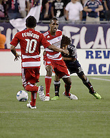 FC Dallas midfielder/forward Atiba Harris(16) battles to prevent New England Revolution defender Kevin Alston (30) from getting at the ball as FC Dallas forward David Ferreira(10) approaches.  The New England Revolution drew FC Dallas 1-1, at Gillette Stadium on May 1, 2010
