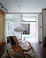 In front of a sliding glass door leading to the outdoor swimming pool a vintage rocking chair in classic 70's style looks completely at home in the architecture of this contemporary house in Florida