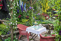 Garden Room Outdoors: Eating outside with wicker chairs, tea set, lush garden, stone patio, coffee cups, luncheon outside on the stone patio with hanging Laburnum, climbing clematis and rose vines, delphinium flowers, achillea, rattan chairs for a colorful private setting amid gorgeous flowers