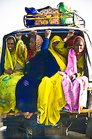 Women in colorful saris traveling in an overloaded three wheeled tuk tuk. (Photo by Matt Considine - Images of Asia Collection)