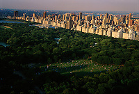 Shadows sweep across Sheep Meadow, a 15-acre space where people congregate for picnics on Sunday afternoon. Until 1934, a shepherd stopped traffic on the west drive so his flock could travel to and from their meadow.  Photograph shows buildings on the east side of Central Park line the perimeter of the park.  The entire perimeter of the park is surrounded by tall buildings and urban life.<br />
