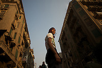 An egyptian protestor stands on top of a barricade during violent clashes with the security forces in central Cairo.