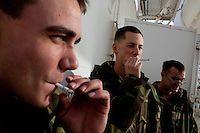 Navy medical personnel take a cigarette break on board the USNS Comfort, a naval hospital ship, as it makes its way to Haiti to help earthquake survivors on Saturday, January 16, 2010 in the Chesapeake Bay.