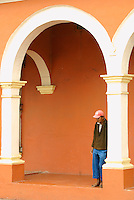 Elderly man standing under a colonnade in the Spanish colonial town of Tlacotalpan,  Veracruz, Mexico. Tlacotalpan is a UNESCO World Heritage Site.              .