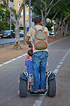 Man & Children On Segway Type Device