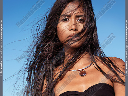 Portrait of a beautiful young woman with long wet dark hair blown in the wind with sky in the background.