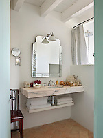 A collection of coral on the marble wash stand gives this fresh, white bathroom a summery and seaside feel