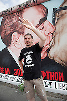 Russian artist Dmitry Vrubel standing in front of his famous Berlin Wall painting of Soviet leader Leonid Brezhnev kissing East German leader Erich Honecker. First painted in 1990, Vrubel, shown here in July 2009, is restoring his painting, after two decades of weathering and graffiti, for the 20th anniversary of the fall of the Berlin Wall in November 2009. .