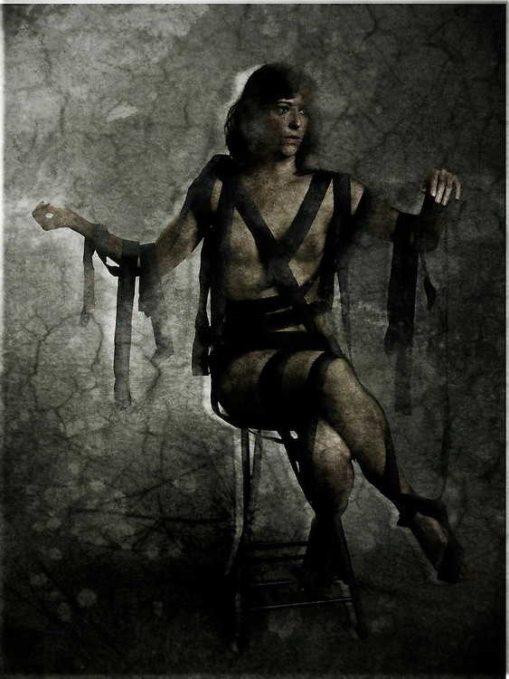 A conceptual image of a naked young woman wrapped in black bandages