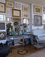 An entire wall of this living room is covered in prints and paintings displayed in antique frames