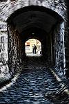 People seen through Alleyway in cobbled street
