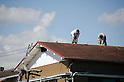 September 23rd, 2011 : Yokohama,  Japan - Japanese men fix the roof after the typhoon No. 15 Roke pasted eastern Japan. (Photo by Yumeto Yamazaki/AFLO)
