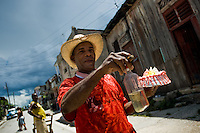 A Cuban man, holding a bottle of rum, smoking a cigar and carrying a sweet cake in his hand, hurries for a fiesta in Santiago de Cuba, Cuba, 3 August 2008. About 50 years after the national rebellion, led by Fidel Castro, and adopting the communist ideology shortly after the victory, the Caribbean island of Cuba is the only country in Americas having the communist political system. Although the Cuban state-controlled economy has never been developed enough to allow Cubans living in social conditions similar to the US or to Europe, mostly middle-age and older Cubans still support the Castro Brothers' regime and the idea of the Cuban Revolution. Since the 1990s Cuba struggles with chronic economic crisis and mainly young Cubans call for the economic changes.