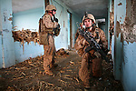 Marines from Company L, 3rd Battalion, 6th Marine Regiment wait inside an abandoned school near Marjah, Afghanistan to see if Taliban fighters will renew their attack. A 20-minute gun battle that ended moments earlier has left one Marine wounded. March 10, 2010. DREW BROWN/STARS AND STRIPES
