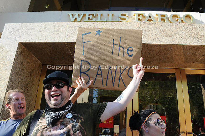Phoenix, Arizona. September 17, 2012 - A small crowd of demonstrators in Phoenix, Arizona gathered to mark one year since the beginning of the Occupy Movement that opposes Wall Street and large corporations that represent the one percent who control wealth in the United States. In this photograph, protesters with the Occupy Phoenix Movement demonstrate against the Wells Fargo Bank in Downtown Phoenix during the first anniversary of the Occupy Wall Street Movement. Photo by Eduardo Barraza © 2012