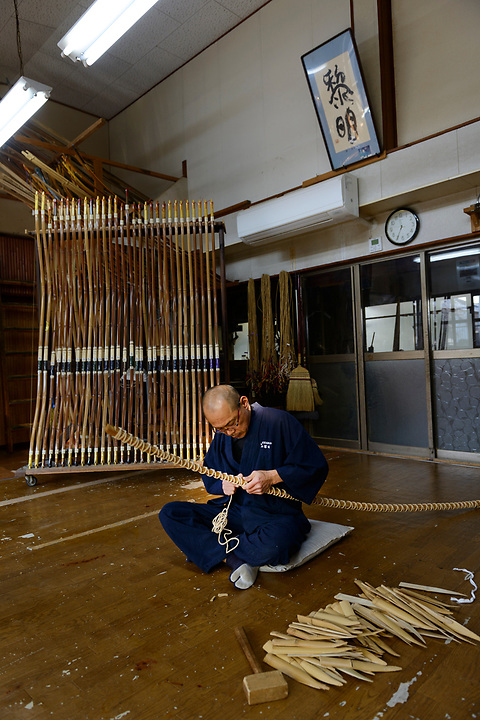 Reimei Yokoyama binding pieces of wood together for laminating as part of the bow making process. Yokoyama Reimei Bowmakers, Miyakonojo, Miyazaki Prefecture, Japan, December 23, 2016. A handful of bowyers from the Kyushu city of Miyakonojo make over 90% of all the bows used in traditional Japanese archery. The bows are made from laminated bamboo and haze wood in process that consists of over 200 individual tasks. At over two meters from tip to tip the bows the longest used in the world.