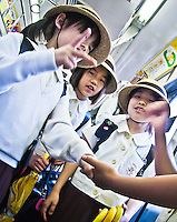 """Tokyo school children head home on the train seen here playing a game of """"scissors-paper-rock""""."""