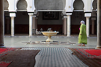 General view of central courtyard with fountain, Moulay Idriss II Mosque, 9th century, Fez, Morocco, pictured on February 21, 2009 in the afternoon. The Mosque of Moulay Idriss II (reigned  803-828), was built by the Idriss dynasty and restored in the 13th century by the Merenids. Containing the mausoleum of Moulay Idriss II, who is believed to aid women's fertility, it is an important pilgrimage destination and a  zaouia or sanctuary. Across the entrance a wooden beam excludes Jews, Christians, and donkeys from the horm, or sacred area around the shrine, where  Moroccans may historically claim sanctuary from arrest. The tomb, covered in brocade and surrounded by the faithful burning candles and incense, is visible through the doors, worn smooth by centuries of pilgrims kissing the wood for baraka or blessing. Fez, Morocco's second largest city, and one of the four imperial cities, was founded in 789 by Idris I on the banks of the River Fez. The oldest university in the world is here and the city is still the Moroccan cultural and spiritual centre. Fez has three sectors: the oldest part, the walled city of Fes-el-Bali, houses Morocco's largest medina and is a UNESCO World Heritage Site;  Fes-el-Jedid was founded in 1244 as a new capital by the Merenid dynasty, and contains the Mellah, or Jewish quarter; Ville Nouvelle was built by the French who took over most of Morocco in 1912 and transferred the capital to Rabat. Picture by Manuel Cohen.