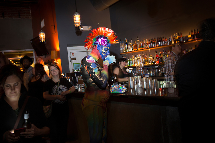 Durham, North Carolina - Sunday May 15, 2016 - Juno Krahn has a drink at the bar at Motorco during the Against Me! show Sunday night in Durham. Krahn was painted by Molly Chopin and MaryBeth Panagos with imagery designed to bring awareness to transgender rights. Against Me! kept their scheduled tour date in Durham and used the show as a platform to protest North Carolina House Bill 2.
