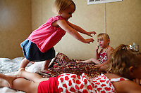 Jayme Smith (left) jumps on the bed with her cousins Hailey Lansaw (middle) and Haylee Malone (below) on August 26, 2011 at their grandmothers FEMA trailer. To make the trailer feel more like Bragole's former home she let the kids pick which room would be theirs every time they came to visit.