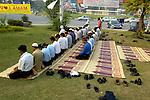 Muslim men pause to pray along a street in Lahore, Pakistan....