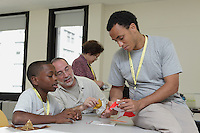 New York, NY, USA - June 23, 2012: Sipho Mabona, Origami designer from Switzerland, teaching a complex bear model during the OrigamiUSA 2012 convention held at Fashion Institute of Technology in New York City. OrigamiUSA members of all ages attend this annual event and take classes to learn various models, classed from simple to highly complex.