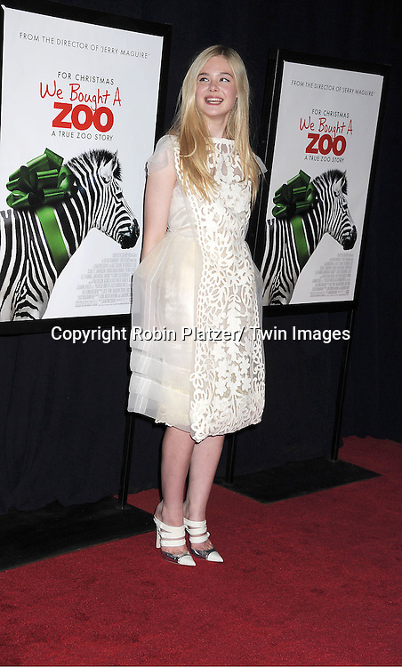 "actress Elle Fanning in Louis Vuitton white cut out dress attends The New York Screening of ""We Bought A Zoo"" on December 12, 2011 at The Ziegfeld Theatre in New York City. The movie stars Matt Damon, Scarlett Johansson, Thomas Haden Church, Patrick Fugit, Colin Ford, Elle Fanning and John Michael Higgins."
