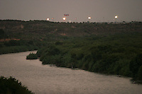 With the Rio Grande River in the foreground, the American flag is seen in the background at the Laredo, Texas border crossing in 2005.