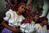 "Salvadoran girls, dressed in typical costumes, pray during the Holy Mass at the end of the Flower & Palm Festival in Panchimalco, El Salvador, 8 May 2011. On the first Sunday of May, the small town of Panchimalco, lying close to San Salvador, celebrates its two patron saints with a spectacular festivity, known as ""Fiesta de las Flores y Palmas"". The origin of this event comes from pre-Columbian Maya culture and used to commemorate the start of the rainy season. Women strip the palm branches and skewer flower blooms on them to create large colorful decoration. In the afternoon procession, lead by a male dance group performing a religious dance-drama inspired by the Spanish Reconquest, large altars adorned with flowers are slowly carried by women, dressed in typical costumes, through the steep streets of the town."