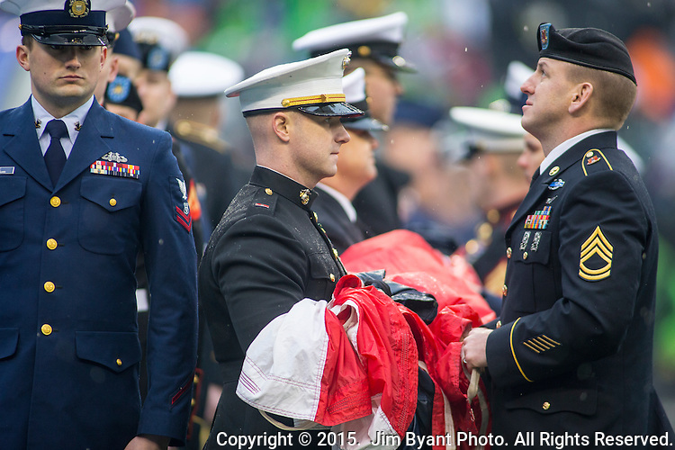 Area Military personnel hands the U.S. Flag before the Seattle Seahawks  vs. Green Bay Packers NFC Championship game at CenturyLink Field in Seattle, Washington on January 18, 2015.  The Seattle Seahawks beat the Green Bay Packers in overtime 28-22 for the NFC Championship Seattle.  ©2015. Photo by Jim Bryant, All Rights Reserved.