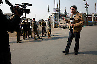 Journalist Mir Fareed reporting on paramilitary police enforcing a curfew imposed to stop separatists gather for a political demonstration in Srinagar, Kashmir, India. © Fredrik Naumann/Felix Features
