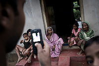 "A villager uses a mobile phone to take a photo of his family in Dhinkia village. All the residents of this village would be displaced if plans for the new steel works are allowed to proceed. South Korean steel giant Posco continues to face stiff public resistance in Orissa's Jagatsinghpur district where the company is setting up India's biggest direct foreign investment project of a 12 million tonne steel plant, at the cost of USD 12 Billion. Villagers have formed an agitating group, ""Posco Pratirdh Sangram Samiti"" to oppose the construction of the Posco development, which will displace thousands of people and make agricultural land untenable."