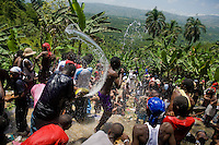 Haitians pilgrims play with water in the waterfall during the annual religious pilgrimage in Saut d'Eau, Haiti, July 16, 2008. Every year in summer thousands of pilgrims from all over Haiti make the religious journey to the Saut d'Eau waterfall (100km north of Port-au-Prince). It is believed that 150 years ago the spirit of Virgin Mary (Our Lady of Mount Carmel) has appeared on a palm tree close to the waterfall. This place became a main pilgrimage site in Haiti since then. Haitians wearing only underwear perform a bathing and cleaning ritual under the 100-foot-high waterfall. Voodoo followers (many Haitians practise both voodoo and catholicism) hope that Erzulie Dantor, the Voodoo spirit of water, manifest itself and they get possessed for a short moment, touched by her presence.