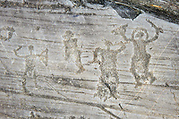 Petroglyph, rock carving, of a warriors with a shields and swords. Carved by the ancient Camunni people in the iron age between  900-1200 BC. Rock no 24, Foppi di Nadro, Riserva Naturale Incisioni Rupestri di Ceto, Cimbergo e Paspardo, Capo di Ponti, Valcamonica (Val Camonica), Lombardy plain, Italy