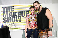 Model with body paint poses with Crown Brush makeup artists, at the Makeup Show NYC, May 15 2011.