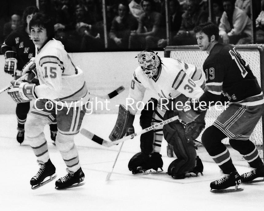 California Golden Seals vs New York Rangers 1974.<br />Jim Neilson, Ranger Jean Ratelle, and Seals goalie Ted Tucker. (photo/Ron Riesterer)