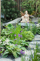 Asian Oriental statue ornament in garden with irises, primroses, pine tree, stone path walkway, in spring blooms
